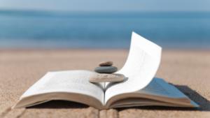 Θερινή Προετοιμασία - Βιβλίο με ανοιχτές σελίδες πάνω στην άμμο στην ακροθαλασσιά.