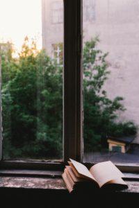 """Για το κείμενό μας """"Οι περιπέτειες της ανάγνωσης"""", το οποίο είναι ένα προτεινόμενο κριτήριο έκθεσης για το ΕΠΑΛ, σύμφωνα με το νέο σύστημα επιλέξαμε μια φωτογραφία του john mark smith, η οποία δείχνει ένα ανοιχτό βιβλίο μπροστά από ένα παράθυρο."""
